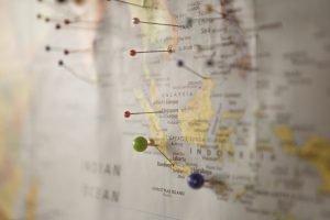Weltkarte mit Nadeln an, die die Reiseziele markieren