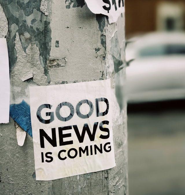 Ein Zettel mit der Aufschrift GOOD NEWS is coming hängt an einer Litfasssäule